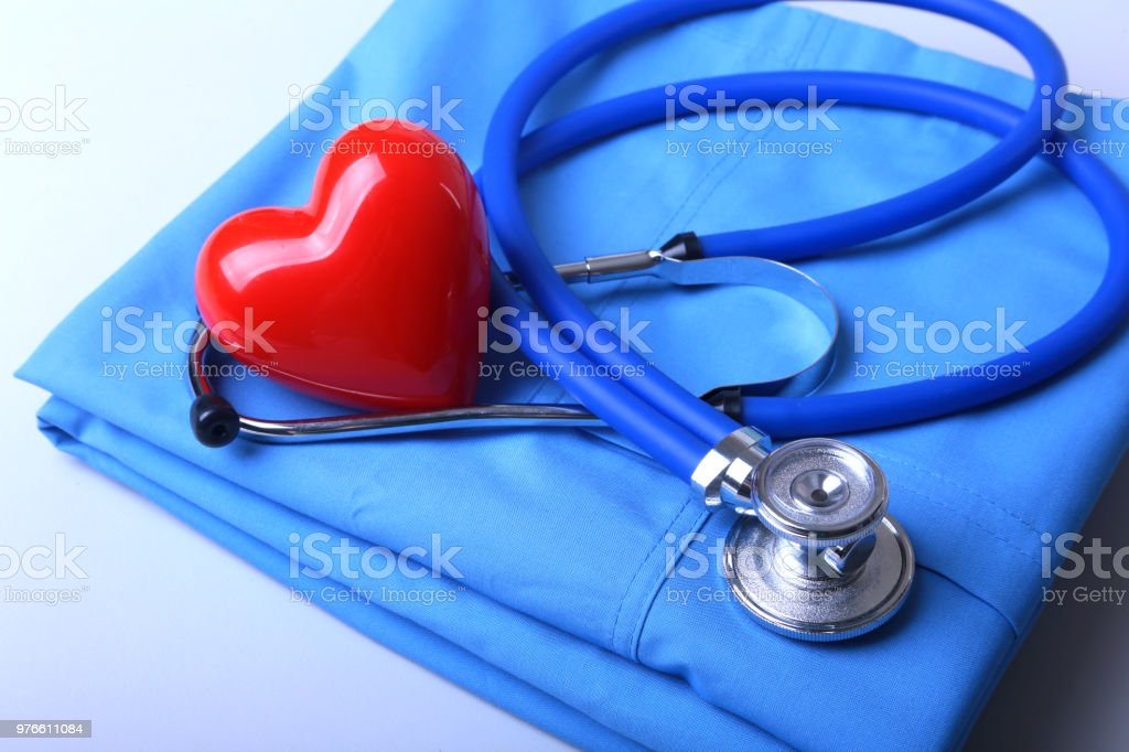 Doctor coat with medical stethoscope and red heart on the desk stock photo