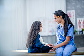 istock Doctor Comforting A Girl 908593530