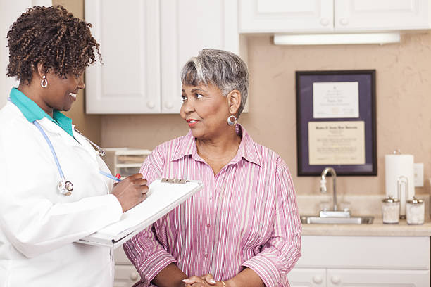 Doctor conducts medical consultation with senior adult patient at clinic. stock photo