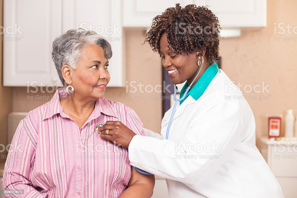 Doctor conducts medical exam on senior adult patient at clinic. stock photo