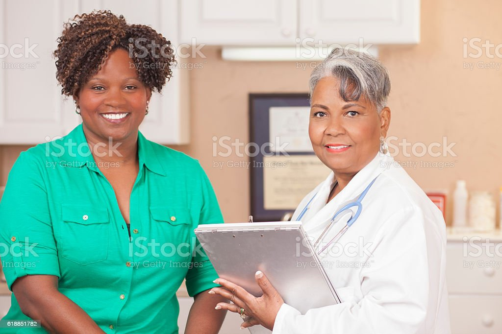African descent, female doctor provides medical exam for mid-adult...
