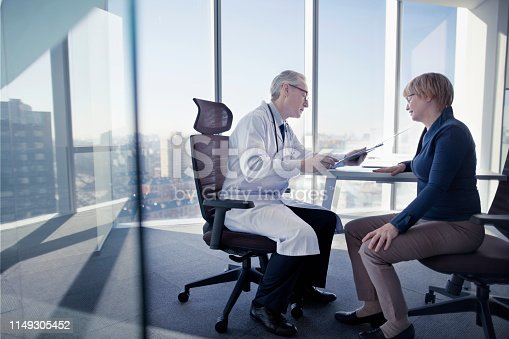 1021670950istockphoto Doctor consoling patient at desk in office 1149305452
