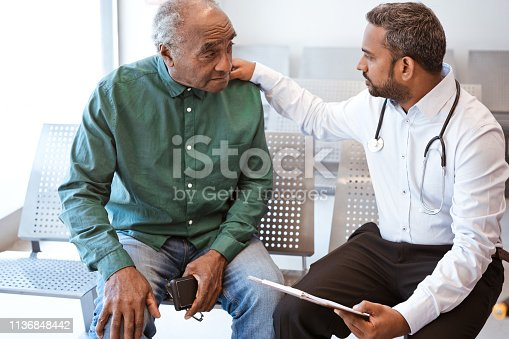 Healthcare worker giving bad news with hand on shoulder of male patient. Doctor consoling sad senior man in waiting room. They are sitting at hospital.