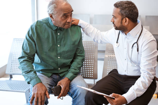 doctor consoling sad senior male patient - elderly patients stock photos and pictures