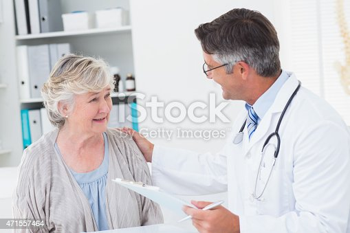 istock Doctor consoling senior woman in clinic 471557464
