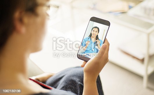 Over the shoulder shot of a patient talking to a doctor using of a mobile phone
