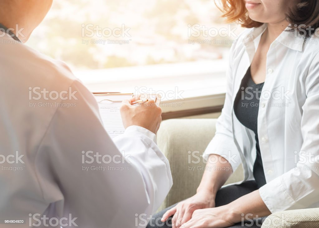 Doctor (obstetrician, gynecologist or psychiatrist) consulting and diagnostic examining female patient's on woman's obstetric - gynecological health in medical clinic or hospital healthcare service center royalty-free stock photo