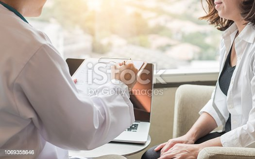 964904920 istock photo Doctor (gynecologist or psychiatrist) consulting and diagnostic examining woman patient's health in medical clinic or hospital healthcare service center 1069358646