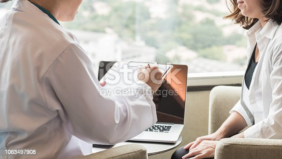 istock Doctor consulting and examining woman patient health in medical clinic or hospital 1063497908
