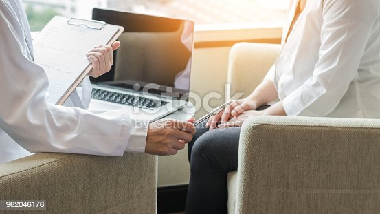istock Doctor consulting and examining woman patient's health in medical clinic or hospital professional service 962046176