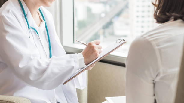 Doctor (gynecologist or psychiatrist) consulting and examining woman patient's health in medical clinic or hospital health service center stock photo