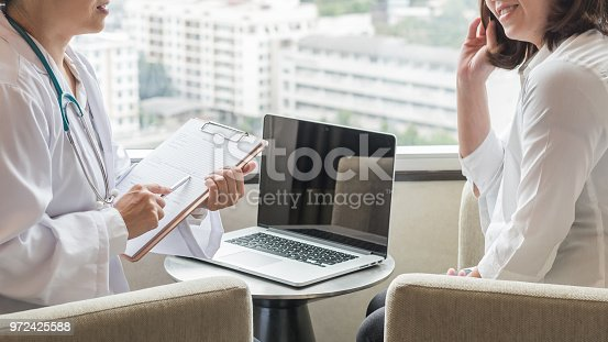 istock Doctor (gynecologist or psychiatrist) consulting and examining woman patient's health in medical clinic or hospital health service center 972425588