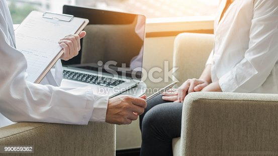 istock Doctor consulting and examining woman patient's health in medical clinic or hospital professional service 990659362