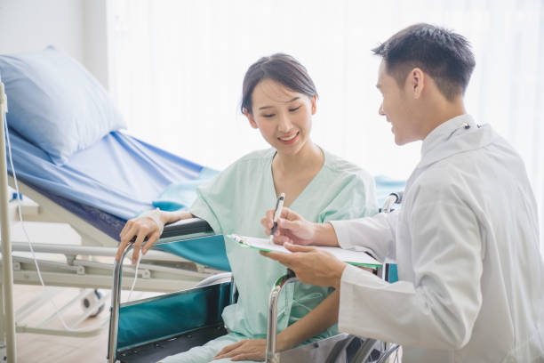 Doctor consulting male patient, working on diagnostic examination on men's health disease or mental illness, and writing on prescription record information document in clinic or hospital office stock photo