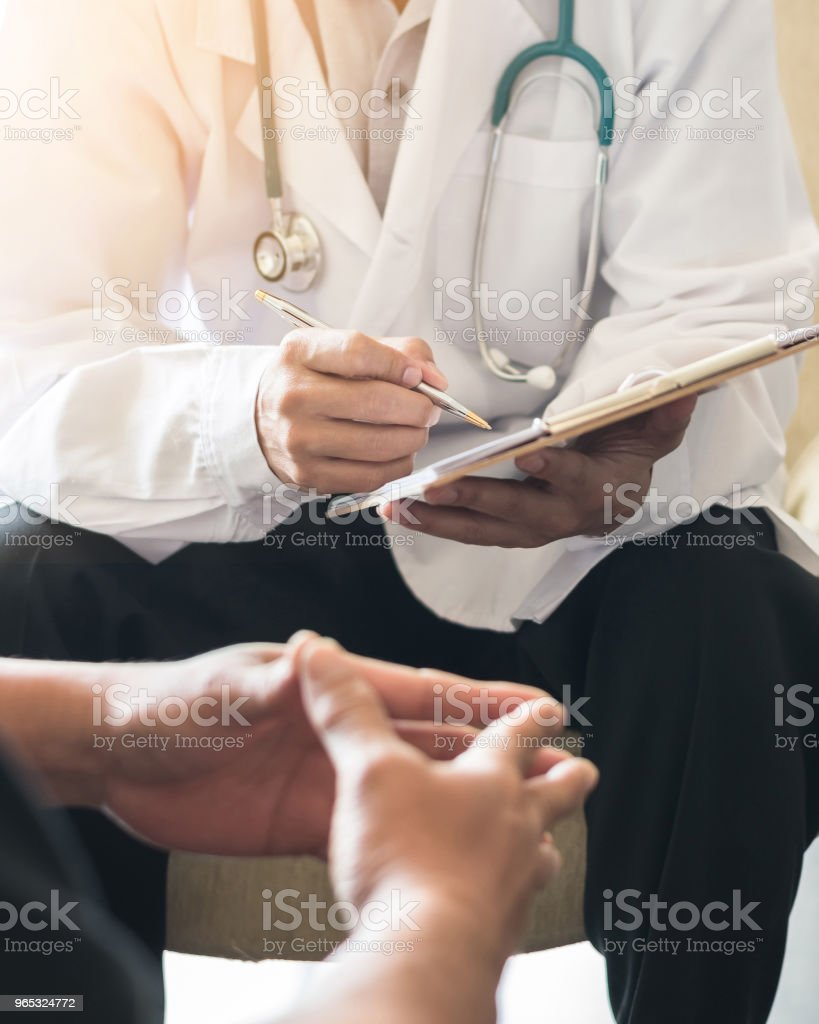 Doctor consulting male patient, working on diagnostic examination on men's health disease or mental illness, and writing on prescription record information document in clinic or hospital office zbiór zdjęć royalty-free