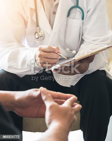 istock Doctor consulting male patient, working on diagnostic examination on men's health disease or mental illness, and writing on prescription record information document in clinic or hospital office 965324772