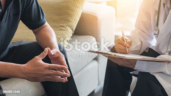 istock Doctor consulting male patient, working on diagnostic examination on men's health disease or mental illness, while writing on prescription record information document in clinic or hospital office 965851348