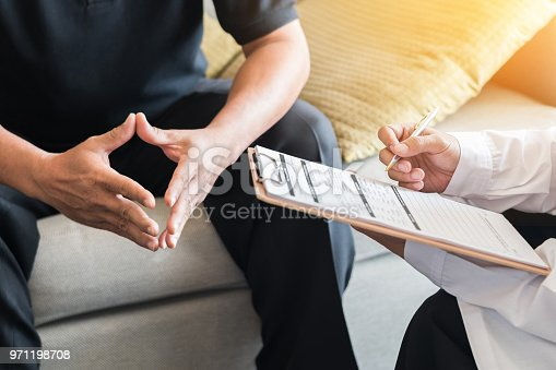 istock Doctor consulting male patient, working on diagnostic examination on men's health disease or mental illness, and writing on prescription record information document in clinic or hospital office 971198708