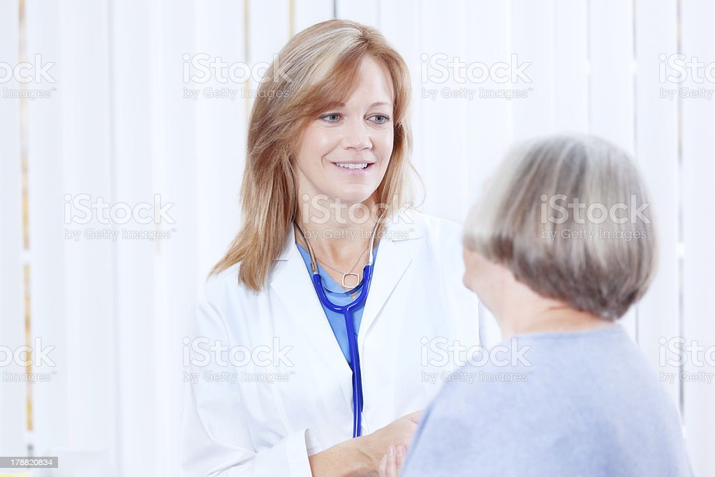 Doctor Consulting Senior Woman Patient in Medical Office Hz royalty-free stock photo