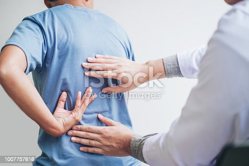istock Doctor consulting with patient Back problems Physical therapy concept 1007757616