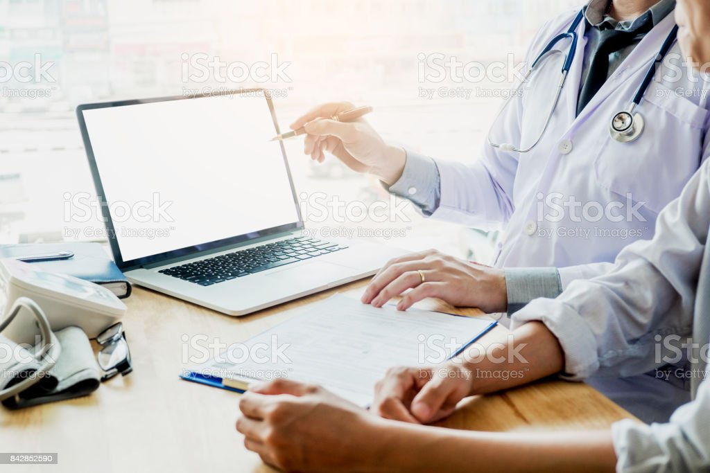 Doctor consulting with patient presenting results on blank Screen tablet computer sitting at table stock photo
