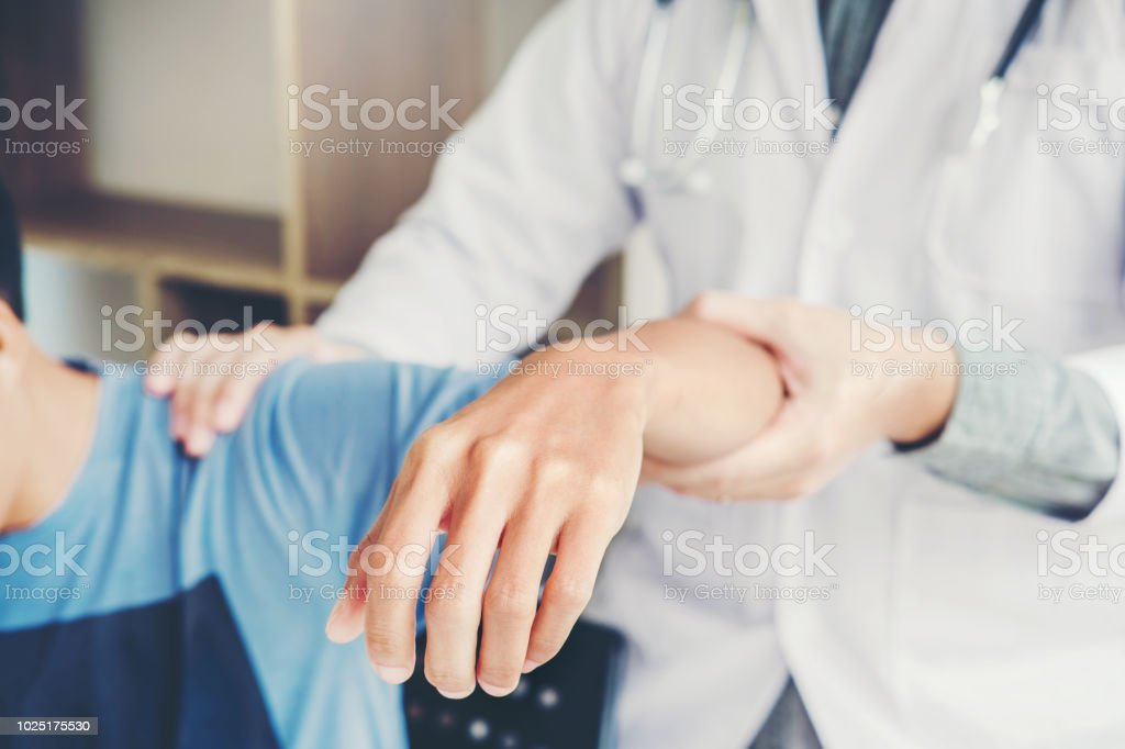 Doctor consulting with patient Shoulder problems Physical therapy diagnosing concept stock photo