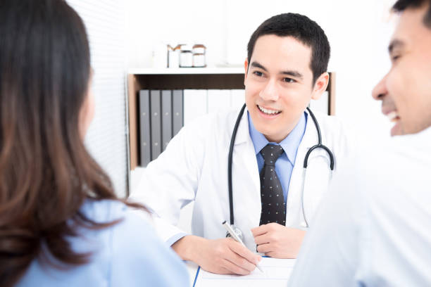 médico consultoria com pacientes do jovem casal - vasectomia - fotografias e filmes do acervo
