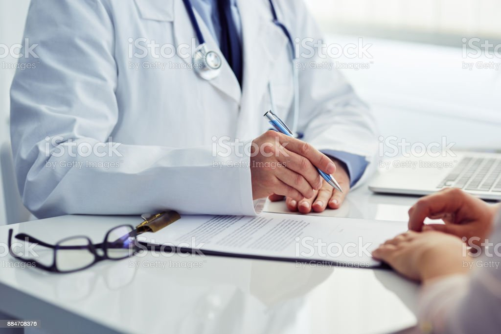 Arzt mit seinem Patienten berät und schreibt Notizen über die Zwischenablage – Foto