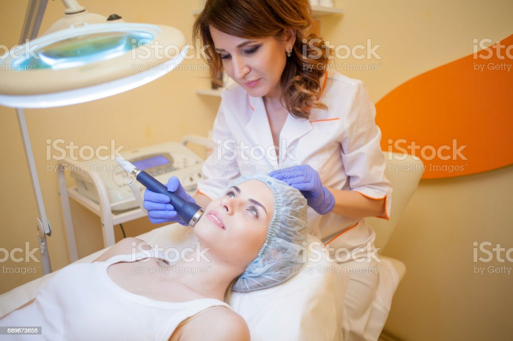 doctor cosmetologist doing procedures on the face stock photo