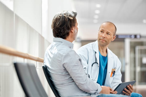 doctor counseling male patient in waiting room - visita foto e immagini stock