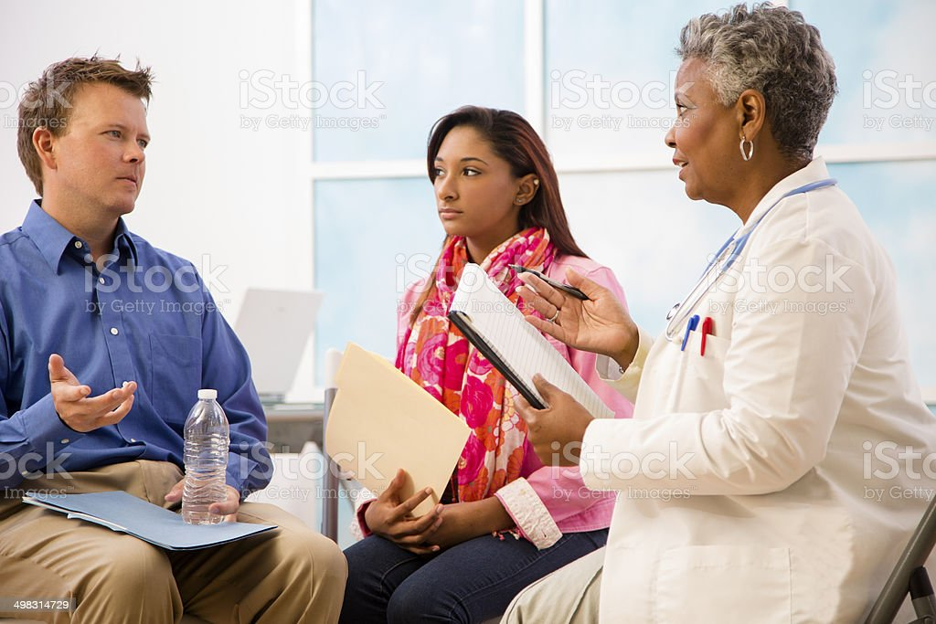 Doctor counseling session with man, woman patients. Therapy. African descent doctor conducts therapy counseling session with caucasian man and mixed-race young woman.  Psychiatrist or medical doctor in office or clinic. 20-29 Years Stock Photo