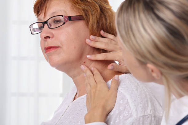Doctor dermatologist examines birthmark of senior woman. Checking benign moles. Laser Skin tags removal stock photo