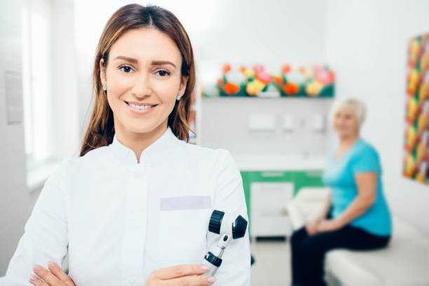 doctor dermatologist with dermatoscope, smiling while looking at camera. behind her sitting senior patient. - dermatologist stock pictures, royalty-free photos & images