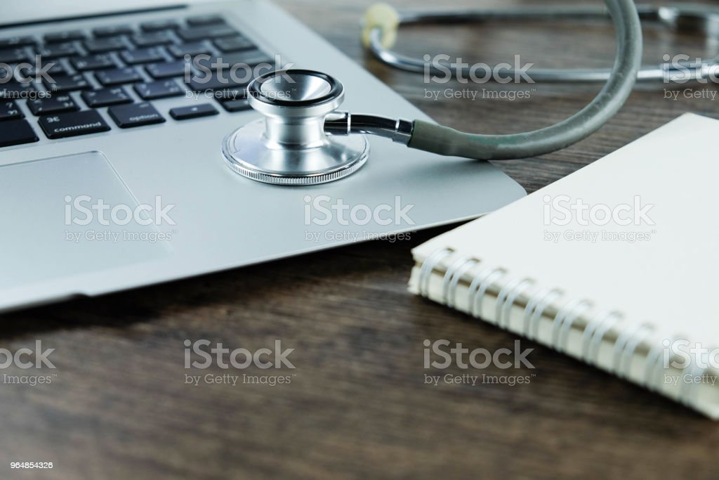 Doctor desk table with stethoscope ,blank notebook and laptop computer on wooden table, medical workspace office. royalty-free stock photo