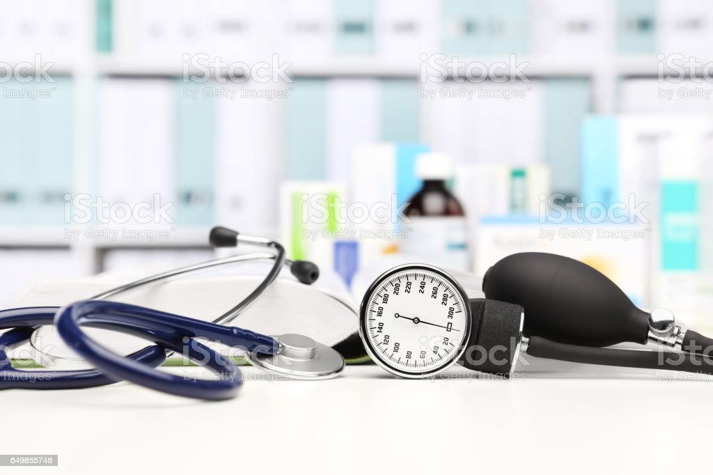 doctor desk with medical equipment, stethoscope and clinic tonometer, blood pressure measurement, drugs in background stock photo