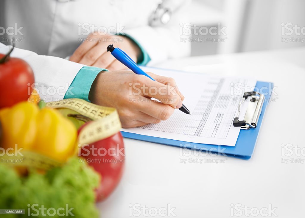 Doctor dietitian writing stock photo