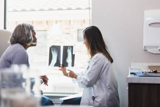 Doctor discusses bone fracture with patient An orthopedic doctor examines a senior woman's bone fracture during a medical appointment. The doctor is reviewing an x-ray image of the woman's foot with the patient. podiatry stock pictures, royalty-free photos & images