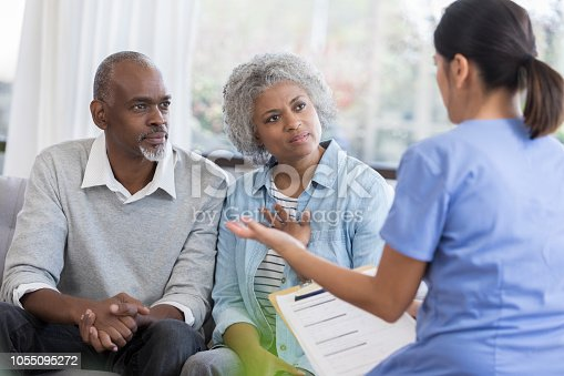 Mid adult female doctor gestures a she discusses a senior couple's health concerns.