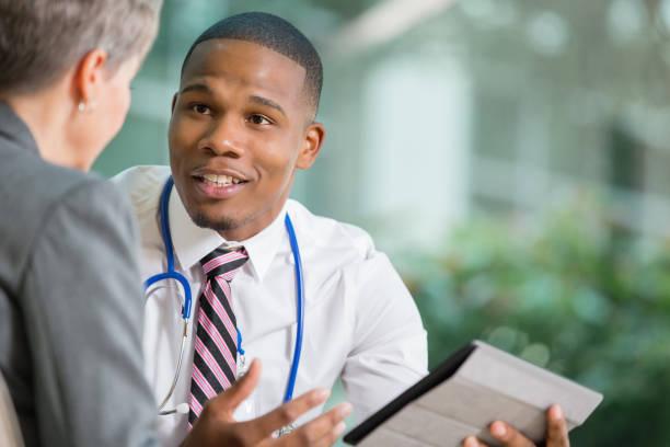 médico a discutir política hospitalar alterações com senior em escritório - senior business woman tablet imagens e fotografias de stock