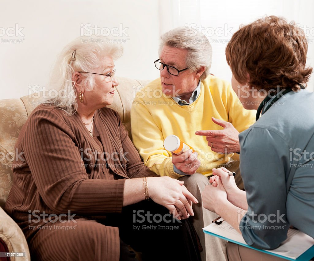 Doctor Discussing Medication with Senior Couple royalty-free stock photo