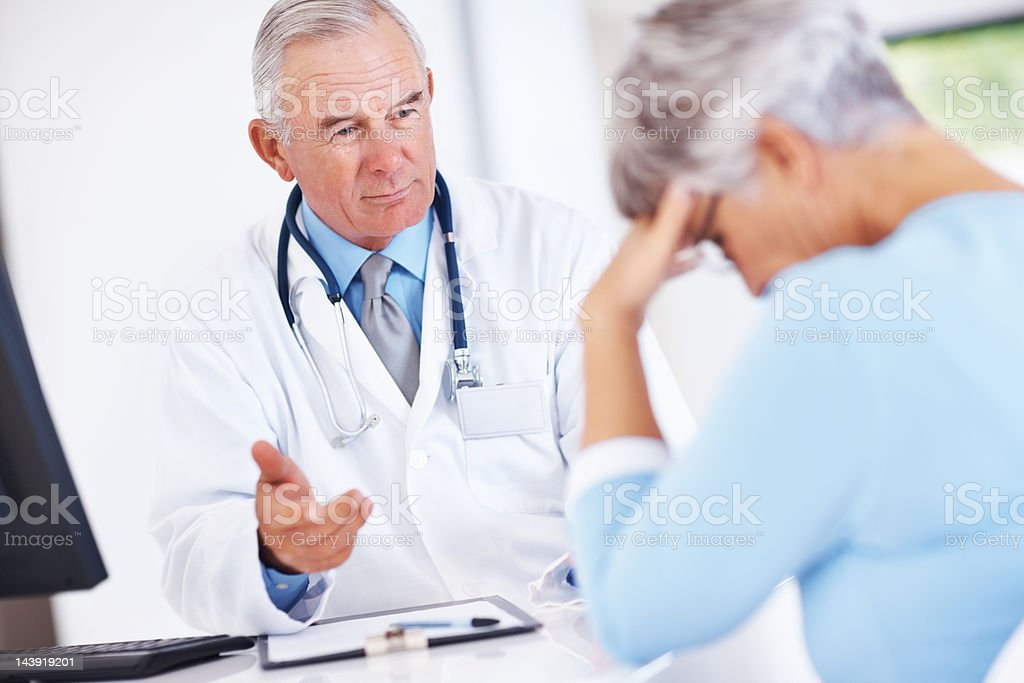 Doctor discussing reports with unhappy patient royalty-free stock photo