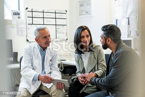 Senior healthcare worker discussing with couple. Male doctor is showing digital tablet to man and woman. They are sitting in hospital.