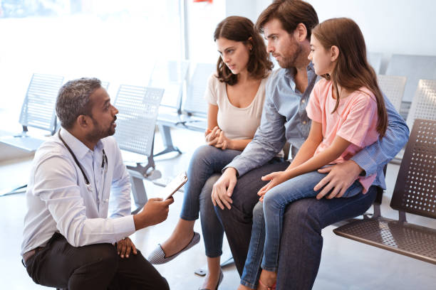 Doctor discussing with girl's family at hospital Doctor kneeling while discussing medical record with patient's parents. Healthcare worker is with girl's family in waiting room. They are talking at hospital. outpatient stock pictures, royalty-free photos & images