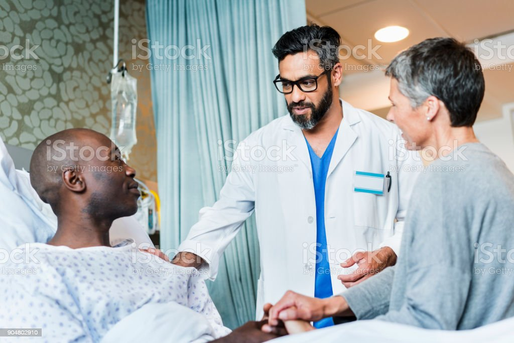 Doctor discussing with patient and woman in ward stock photo