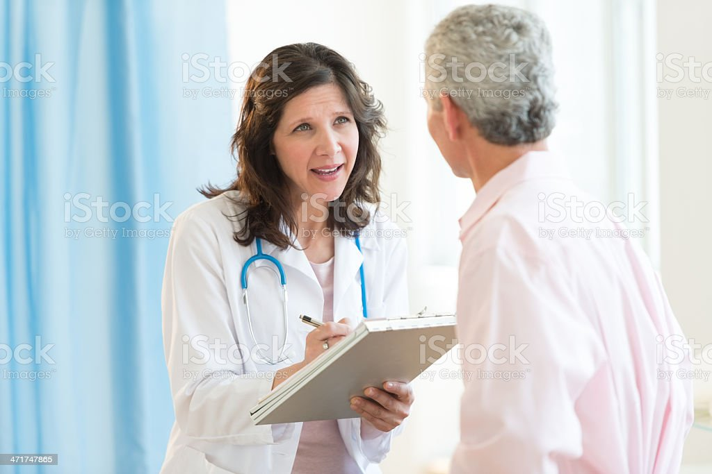 Doctor Discussing With Patient In Hospital stock photo