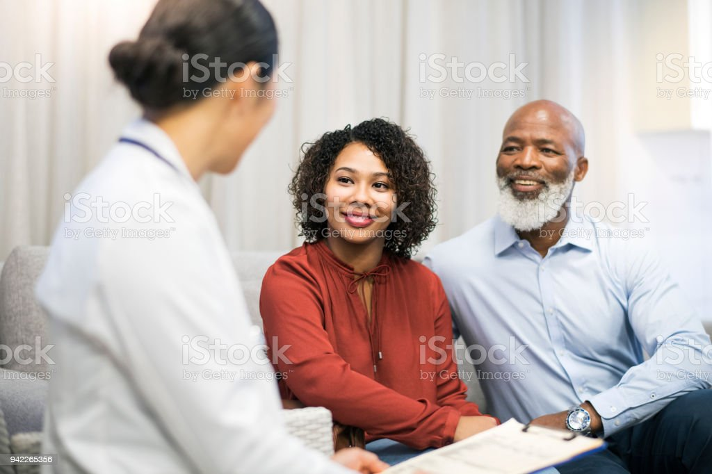 Doctor discussing with patient on sofa in clinic stock photo