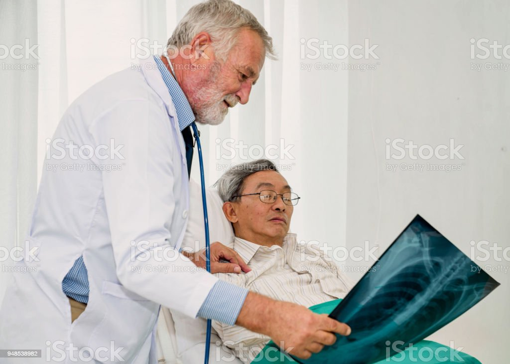 Doctor discussing x-ray image with patient. stock photo