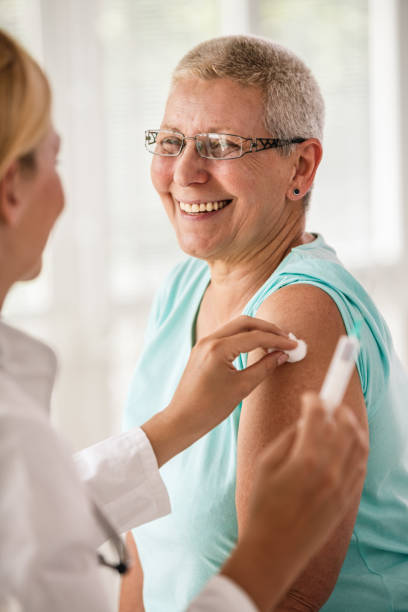 Doctor disinfecting patient's arm before vaccination stock photo