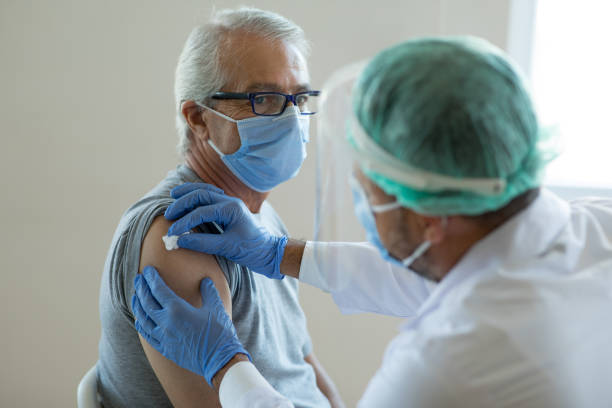 Doctor disinfecting patient's skin for vaccination stock photo