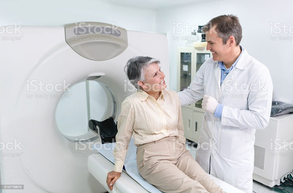 Doctor doing a CAT scan on a senior woman at the hospital - radiology...